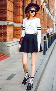 简约的圆领套头毛衣,黑色条纹拼接,白色简约而纯净,有着别样的味道。搭配黑色绑带半身裙,街头欧美潮范。